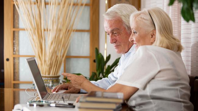 Older couple interacting with a laptop