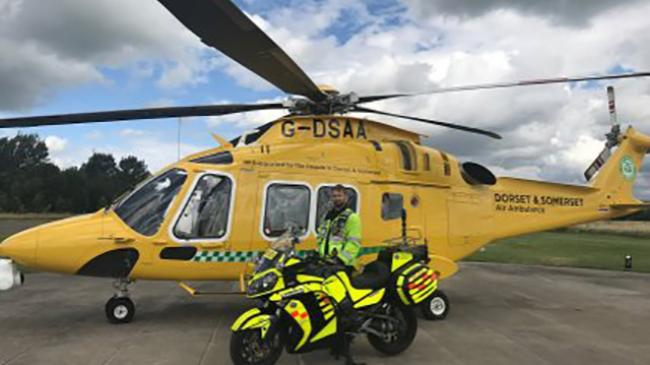 Emergency biker Trevor Rule with the new Helimed aircraft in Dorset